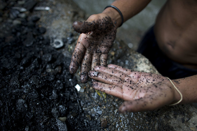 In this November 30, 2017 photo, a river scavenger shows a silver cross he found at the bottom of the polluted Guaire River, in Caracas, Venezuela. Scavengers rake their hands across the river bottom and let the gravel and rocks fall through their fingers, scanning for an earring backing, lost rings or any bits of precious metal to cash in for food. (Photo by Ariana Cubillos/AP Photo)