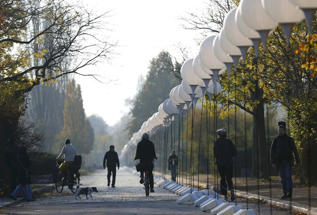 """People cycle along stands with balloons placed along the former Berlin Wall location at Mauerpark, which will be used in the installation """"Lichtgrenze"""" (Border of Light) in Berlin November 7, 2014. (Photo by Pawel Kopczynski/Reuters)"""