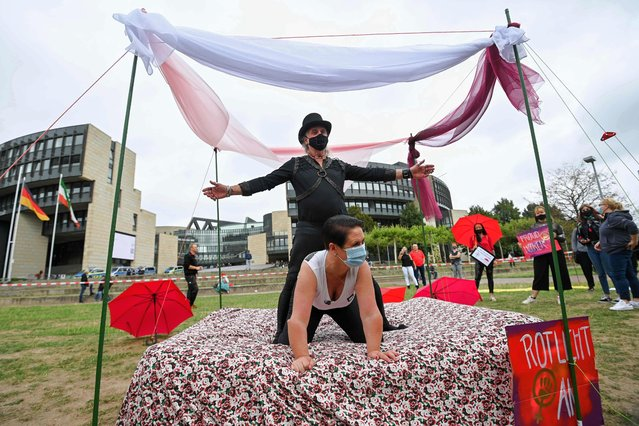 Sеx workers demonstrate how they could carry out their work under corona conditions with the hygiene concept during a protest to demand the reopening of brothels amid the new coronavirus pandemic at the State Parliament in Duesseldorf, western Germany, on August 27, 2020. (Photo by Ina Fassbender/AFP Photo)