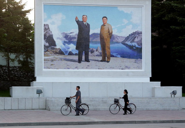 Locals push their bicycles past a large painting depicting North Korean leaders Kum Il Sung, left, and Kim Jong Il in Wonsan, North Korea, Monday, August 17, 2015. The port city on the country's east coast is a popular destination for foreign and local vacationers. (Photo by Dita Alangkara/AP Photo)