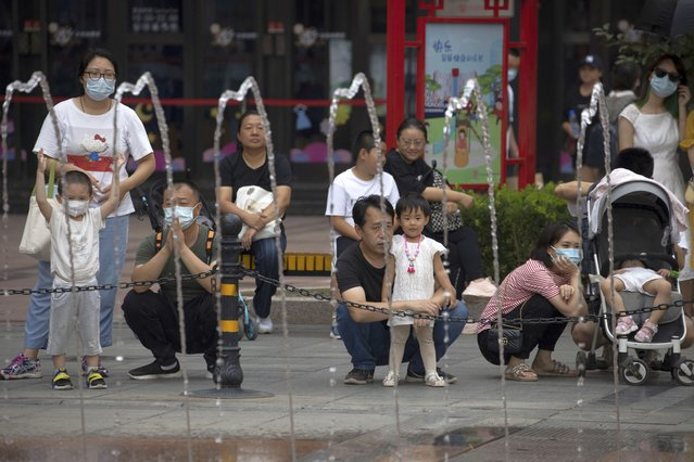 Residents wearing mask to protect from the coronavirus watch a water fountain at a retail street in Beijing, China on Saturday, August 29, 2020.  About one-third of students returned to school in the Chinese capital on Saturday in a staggered start to the new school year because of the coronavirus. (Photo by Ng Han Guan/AP Photo)