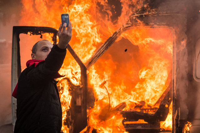 A protestor makes a selfie in front of a burning car during a national trade union demonstration in Brussels, Thursday November 6, 2014. Tens of thousands of demonstrators are converging on the Belgian capital to protest government policies that will extend the pension age, contain wages and cut into public services. (Photo by Geert Vanden Wijngaert/AP Photo)