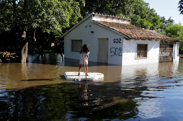 A young girl uses a piece of styrofoam as a paddle board next to a flooded home after heavy rains caused the river Paraguay to overflow, on the outskirts of Asuncion, Paraguay January 23, 2018. (Photo by Jorge Adorno/Reuters)