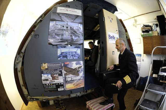 Igor Perne, 53, an electronic engineer and a member of the International Virtual Aviation Organisation (IVAO), steps into his flight simulator in Nova Vas November 13, 2014. (Photo by Srdjan Zivulovic/Reuters)
