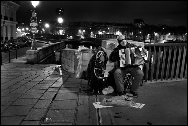 On a bridge in Paris on a cold November night, a lone man sits and plays a song. His song, is our song and our night is better for it. (Photo and comment by Peter Turnley)