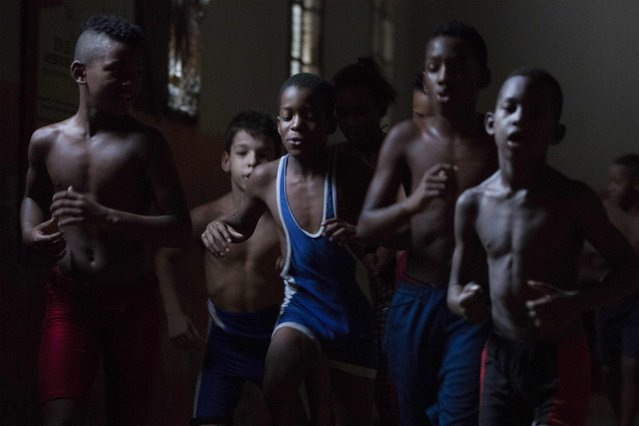 Children exercise during a wrestling lesson at an old Basque ball gymnasium in downtown Havana, October 23, 2014. (Photo by Alexandre Meneghini/Reuters)