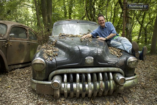 Michael sat on the bonnet of his rotting Buick car worth £13,000 in Neandertal Germany, September 11, 2016. (Photo by Christoph Hagen/Barcroft Images)