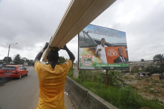 A man carrying wood planks passby the campaign billboard of presidential candidate Alassane Ouattara of the ruling RHDP coalition  in Adjame district, Abidjan October 19, 2015. (Photo by Thierre Gouegnon/Reuters)