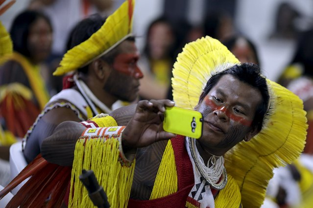 An indigenous man from the Kayapo tribe takes a picture as he arrives to participate in the I World Games for Indigenous People in Palmas, Brazil, October 20, 2015. (Photo by Ueslei Marcelino/Reuters)