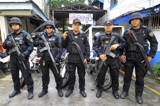 Members of the Philippine National Police Special Weapons and Tactics (SWAT) team pose for a picture outside a police station in Manila September 15, 2014. (Photo by Romeo Ranoco/Reuters)