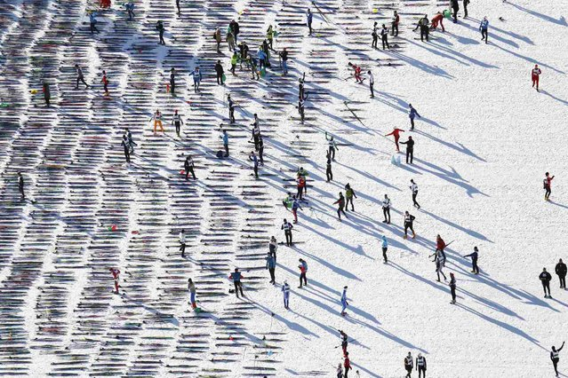 An aerial view shows cross-country skiers awaiting the start of the Engadin Ski Marathon on the frozen Lake Sils near the village of Maloja March 10, 2013. More than 12,000 skiers participated in the 42.2 km (26.2 miles) race between Maloja and S-chanf near the Swiss mountain resort of St. Moritz. (Photo by Michael Buholzer/Reuters)