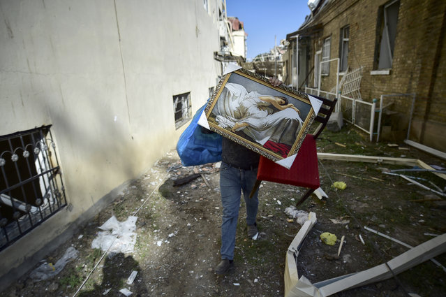 A man carries belongings from his damaged house two days after shelling by Armenian's artillery during fighting over the separatist region of Nagorno-Karabakh, in Ganja, Azerbaijan, Tuesday, October 13, 2020. Azerbaijan has accused Armenia of attacking large cities Sunday overnight in violation of the cease-fire deal brokered by Russia that seeks to end the worst outbreak of hostilities in the separatist Nagorno-Karabakh region. (Photo by Ismail Coskun/IHA via AP Photo)