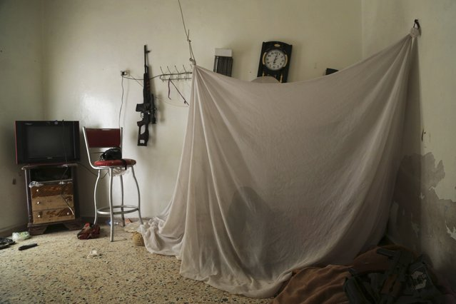 A rebel fighter rests inside a room on the Karm al-Tarab frontline in Aleppo, in this July 30, 2014 file photo. (Photo by Hamid Khatib/Reuters)