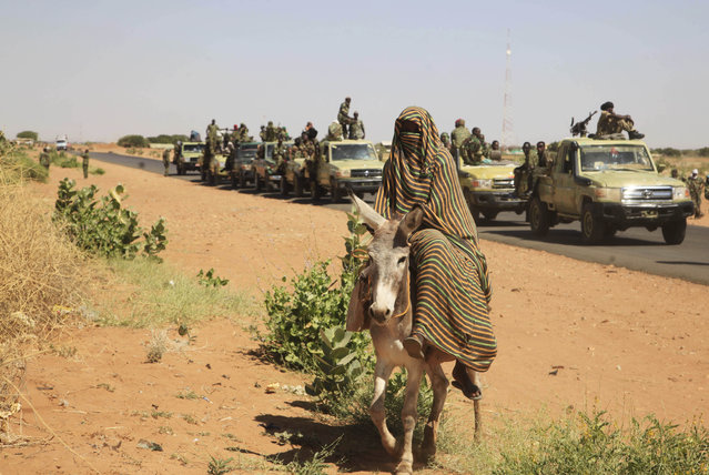In this Thursday, November 20, 2014 photo taken on a government organized media tour, a woman rides a donkey past a convoy of government troops in Tabit village in the North Darfur region of Sudan, where allegations surfaced of rape of women by government allied troops. A Human Rights Watch report released Wednesday, Sept. 9, 2015 is accusing the Sudanese military of another mass rape in Darfur. According to the report, members of Sudan's Rapid Support Forces raped at least 60 women in the country's troubled western region, after taking over the town of Golo in January. It says many women were attacked in a hospital where people had taken shelter. (Photo by Abd Raouf/AP Photo)