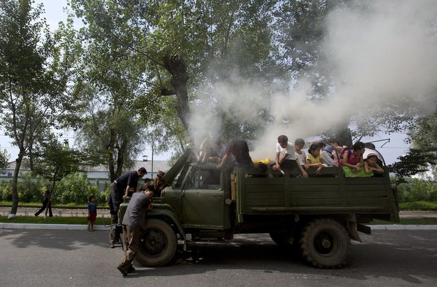 A truck, retrofitted to run on a barrel of burning wood, stops on a road in Hamhung, North Korea, on August 11, 2012. (Photo by David Guttenfelder/AP Photo)