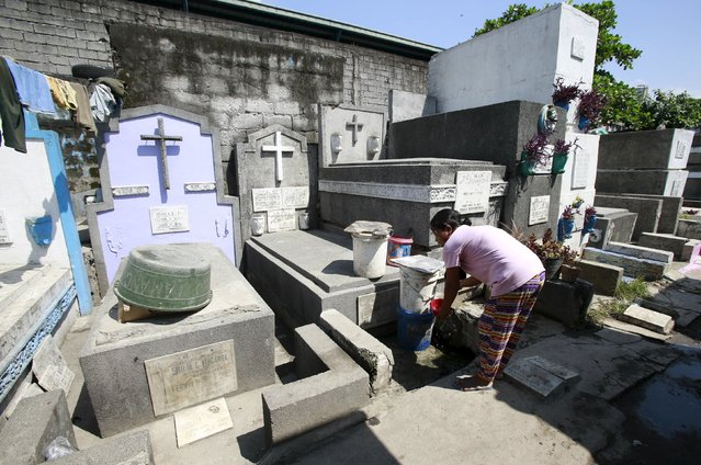 A woman living inside the cemetery washes her hands near the tombs at the Manila South Public Cemetery in Pasay City, metro Manila October 30, 2015. (Photo by Romeo Ranoco/Reuters)
