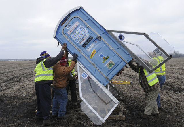 Members of the Michiana Rocketry prep a 10-foot, 450 pound porta-potty, mounted on rocket motors for launching, Saturday, December 6, 2014, from a field in Three Oaks, Mich. (Photo by Don Campbell/AP Photo/The Herald-Palladium)