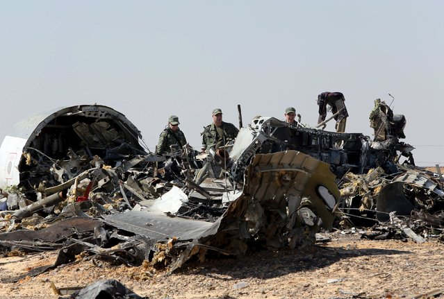 Military investigators from Russia stand near the debris of a Russian airliner at the site of its crash at the Hassana area in Arish city, north Egypt, November 1, 2015. (Photo by Mohamed Abd El Ghany/Reuters)