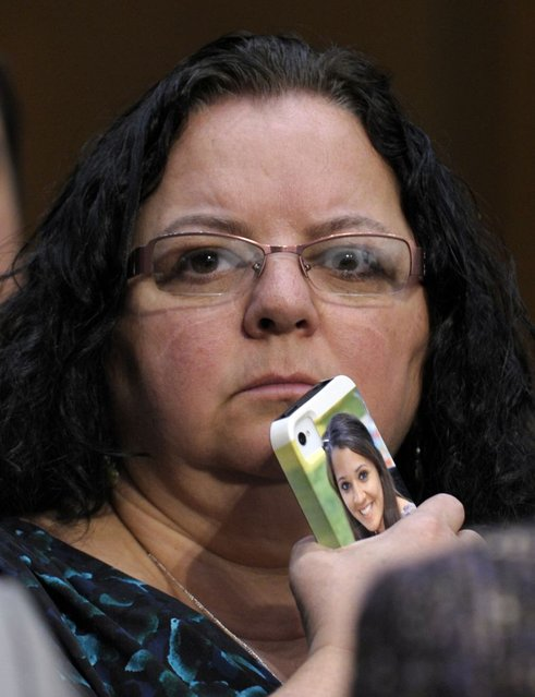 Donna Soto, mother of slain Sandy Hook Elementary teacher Victoria Soto, holds here phone with a photo of her daughter on it while she listens to testimony on Capitol Hill in Washington, Wednesday, February 27, 2013, during the Senate Judiciary Committee on the Assault Weapons Ban of 2013. (Photo by Susan Walsh/AP Photo)