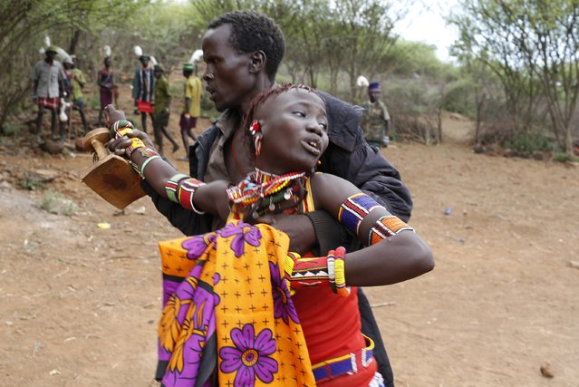 A man grabs a girl to bring her back to her family home after she tried to escape when she realised she is to be married, about 80 km (50 miles) from the town of Marigat in Baringo County December 7, 2014. (Photo by Siegfried Modola/Reuters)