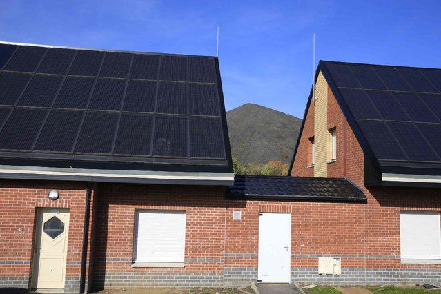 Houses with roofs covered with solar panels are seen near the 11/19 pit and twin slag heaps (rear) at the former coal mine site in Loos-en-Gohelle, northern France October 31, 2015. (Photo by Pascal Rossignol/Reuters)