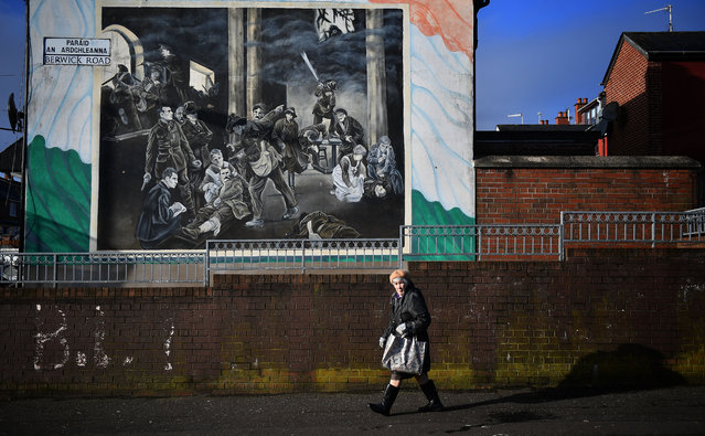 A woman walks past a dual Irish-English language street sign on February 21, 2018 in Belfast, Northern Ireland. Talks to restore the Northern Ireland power sharing executive collapsed last week with the main sticking point being a proposed Irish language act. A leaked draft agreement between Sinn Fein and the DUP confirmed a three-stranded approach to the language question, which would have resulted in an Irish language act, an Ulster-Scots act and a so-called respecting language and diversity act. The province has been without a government for over 13 months since then deputy First Minister Martin McGuinness resigned his position in protest at a botched renewable heating scheme. (Photo by Charles McQuillan/Getty Images)