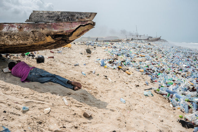 """A man takes a rest in the shade on a litter-strewn beach in Accra, Ghana on January 21, 2018, close to Africa's biggest waste disposal site, also called by the locals with the biblical name of """"Sodoma and Gomorra"""". (Photo by Maniglia Romano/Pacific Press/Barcroft Images)"""