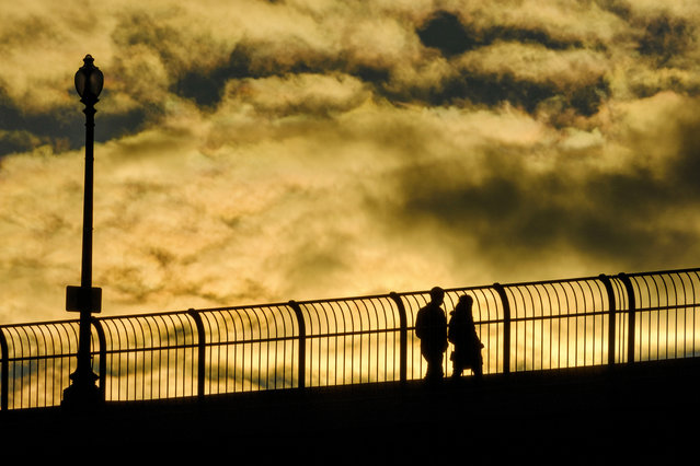 A couple walks across the Francis Scott Key Bridge as the setting sun lights up the clouds in Washington, Friday, October 30, 2020. (Photo by J. David Ake/AP Photo)
