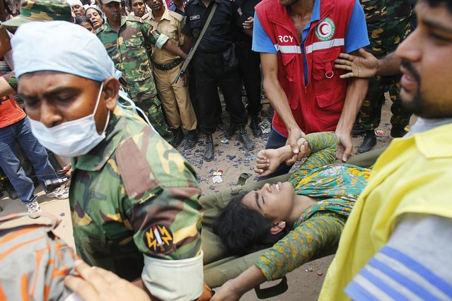 Rescue workers carry a survivor, who was trapped inside the rubble of the collapsed Rana Plaza building, in Savar, 30 km (19 miles) outside Dhaka April 25, 2013.  The death toll from a building collapse in Bangladesh has risen to 160 and could climb higher, police said on Thursday, with people trapped under the rubble of a complex that housed garment factories supplying retailers in Europe and North America. (Photo by  Andrew Biraj/Reuters)