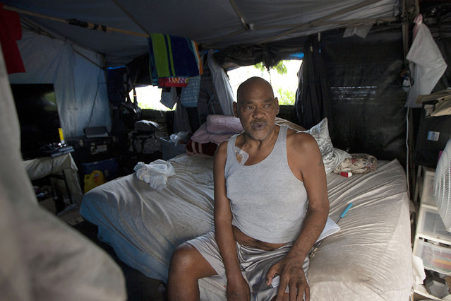 In this July 21, 2015 photo, Cheyenne Suka sits on his bed in a homeless encampment in the Kakaaako neighborhood of Honolulu. Suka ran a general store out of his tent to help pay for living on the streets until the city recently removed the large homeless encampment, forcing its residents to find new shelter. (Photo by Jae C. Hong/AP Photo)