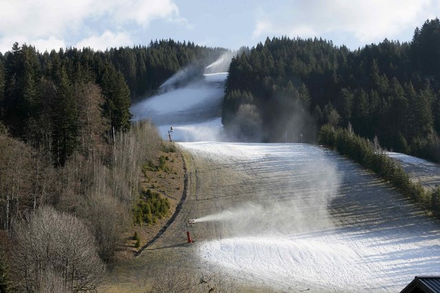 Artificial snow making machines operate on grass-covered slopes at the ski station at Les Gets in the French Alps December 26, 2014. Meteo France weather service predicts snowfall in France over the weekend according to media reports. (Photo by Gonzalo Fuentes/Reuters)