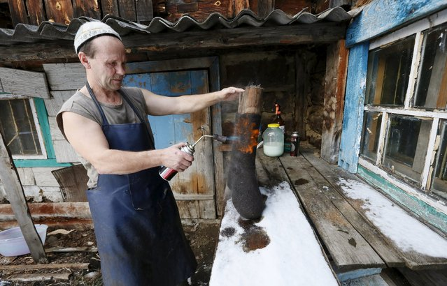 Ivan Plakhuta, 54, the owner of a small workshop manufacturing valenki, Russian traditional footwear, burns a valenok to make it smooth in the remote Siberian village of Bolshaya Rechka, located in Taiga area in the foothills of the Western Sayan Mountain Ridge in the Yermakovsky district of Krasnoyarsk region, Russia, November 10, 2015. (Photo by Ilya Naymushin/Reuters)