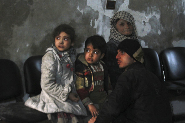 Injured children wait in a field hospital after what activists said was was an air strike by forces loyal to Syria's President Bashar al-Assad in the Duma neighbourhood of Damascus, December 21, 2014. (Photo by Badra Mamet/Reuters)