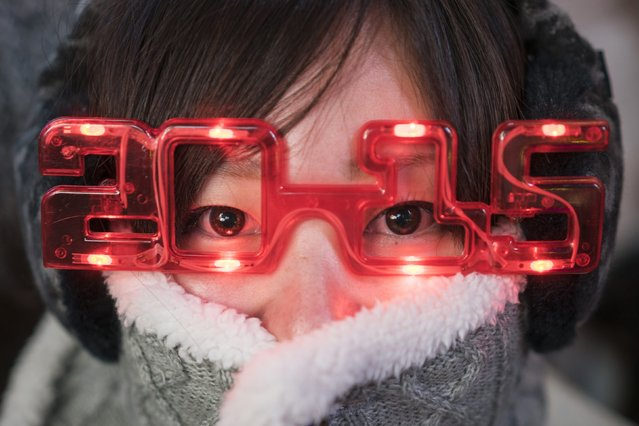 A woman sports 2015 glasses while taking cover from the cold weather during New Year's Eve celebrations in Times Square, New York December 31, 2014. (Photo by Zoran Milich/Reuters)