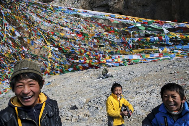 Tibetan boys smile in front of prayer flags place on a rock over Namtso lake in the Tibet Autonomous Region, China November 18, 2015. (Photo by Damir Sagolj/Reuters)