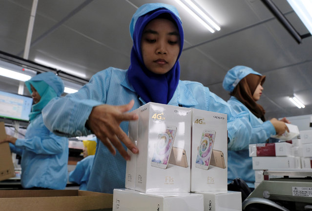 Workers hold packs of OPPO F1s smartphones at the OPPO smartphone factory in Tangerang, Indonesia, September 20, 2016. (Photo by Reuters/Beawiharta)