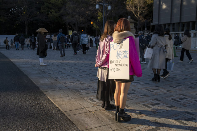 A couple of women advertises for PCR testing for COVID-19 near the front entrance gate for Maiji Jingu Shinto Shrine Friday, January 1, 2021, in Tokyo, as people arrive any the shrine to pray for good fortune in the new year. Meiji Shrine in downtown Tokyo, which attracts millions of people every year during New Year holidays and is usually open all night on New Year's Eve, was closed its doors from 4 p.m. on Dec. 31 to 6 a.m. this year to avoid cluster. This was the first time the popular shrine closed its door on New Year's Eve night in 74 years. (Photo by Kiichiro Sato/AP Photo)