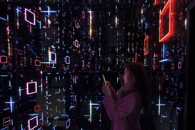 "A woman takes pictures as she views an exhibition called ""Oh! Future Sensation"" as part of Saint-Gobain's 350th anniversary celebrations in Shanghai January 13, 2015. (Photo by Aly Song/Reuters)"