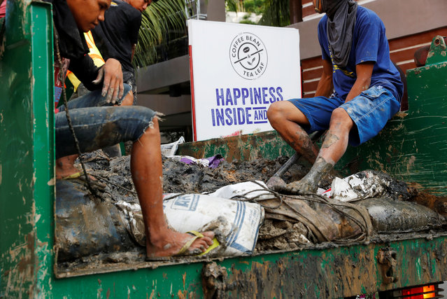 Filipino workers ride in a truck with waste materials collected from clogged sewage drainage pipes from the main road of Boracay island, in Philippines April 10, 2018. (Photo by Erik De Castro/Reuters)