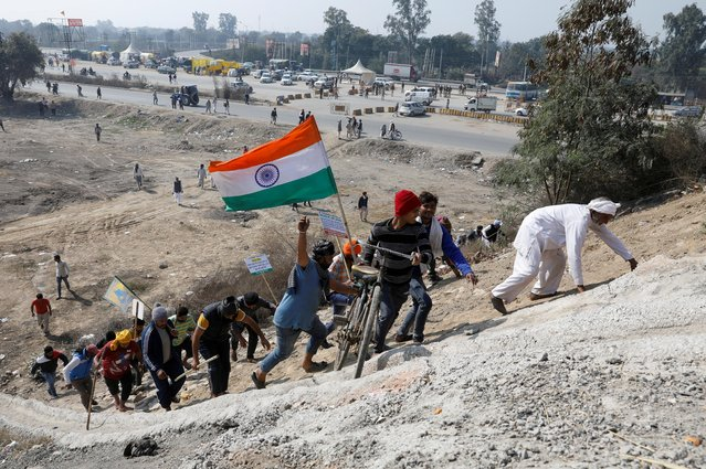 """Farmers climb up a hill as they take part in a three-hour """"chakka jam"""", or road blockade, as part of protests against farm laws on a highway on the outskirts of New Delhi, India, February 6, 2021. (Photo by Adnan Abidi/Reuters)"""