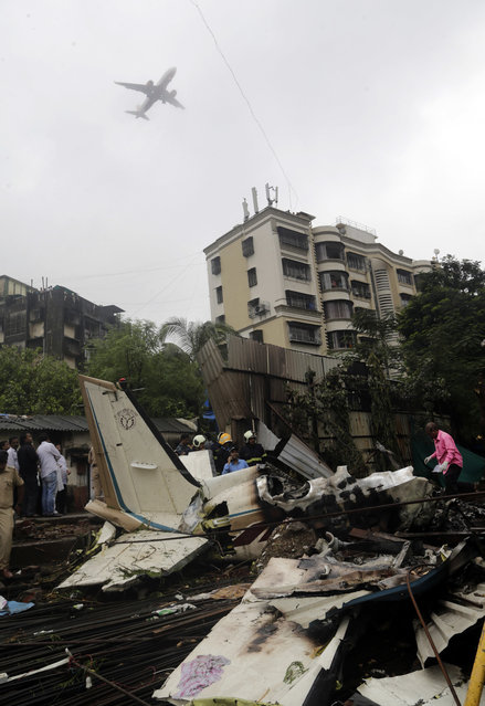 In this Thursday, June 28, 2018, file photo, an aircraft flies above as rescuers stand amid the wreckage of a private chartered plane that crashed in Ghatkopar area, Mumbai, India. The plane hit an open area at a construction site for a multistory building in a crowded area with many residential apartments. At least six people including two on the ground were killed. (Photo by Rajanish Kakade/AP Photo/File)