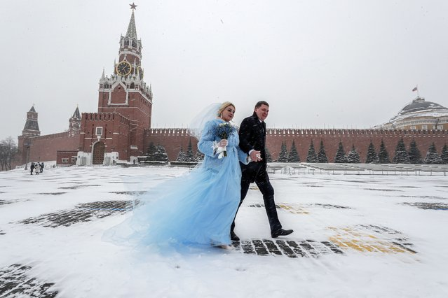 Newlyweds walk on Red Square during a snowfall in Moscow, Russia, 12 February 2021. Moscow was struck by a powerful snowfall, which is expected to continue during the next three days. Temperatures in the Russian capital dropped to minus 15 degrees Celsius. (Photo by Sergei Ilnitsky/EPA/EFE)