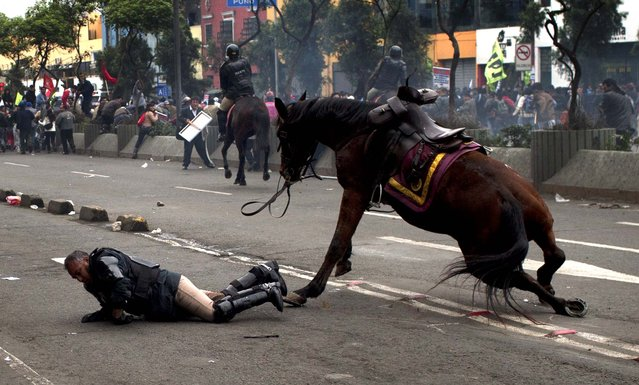 A policeman tries to recover after falling from his horse during a protest against the new civil service law that will require government employees to undergo work evaluations, in Lima, Peru, on July 4, 2013. After a total of 20 hours of debates and months of modifications, Peru's Congress approved the new civil service law with 59 votes in favor, 45 against and 3 abstentions. (Photo by Rodrigo Abd/Associated Press)