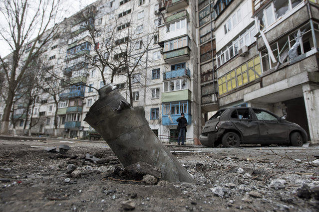 A piece of an exploded Grad missile is photographed outside an apartment building in Vostochniy, district of Mariupol, Eastern Ukraine, Sunday, January 25, 2015. (Photo by Evgeniy Maloletka/AP Photo)