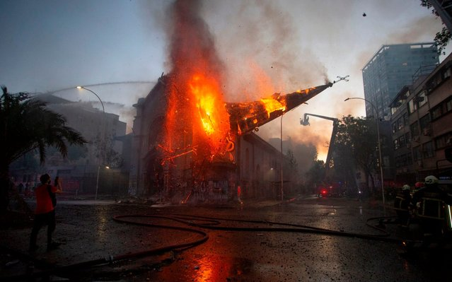 The dome of the church of Asuncion falls down burning in flames after being set on fire by demonstrators on the commemoration of the first anniversary of the social uprising in Chile, in Santiago, on October 18, 2020, as the country prepares for a landmark referendum. (Photo by Claudio Reyes/AFP Photo)