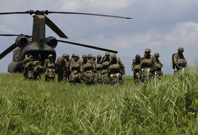 Japanese Ground Self-Defense Force's 1st Airborne Brigade soldiers prepares to board a CH-47 helicopter for a parachute drop training during their military drill at Higashifuji training field in Susono, west of Tokyo, July 8, 2013. Japan faces increasingly serious threats to its security from China and North Korea, a defence ministry report said on Tuesday, as ruling politicians call for the military to beef up its ability to respond to such threats. (Photo by Issei Kato/Reuters)