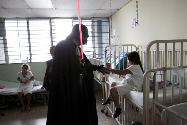 A cosplayer dressed as Darth Vader from the Star Wars movie series interacts with a girl during a charity event organised by the El Salvador Star Wars fan club at the Benjamin Bloom National Children's Hospital in San Salvador, El Salvador December 14, 2015. (Photo by Jose Cabezas/Reuters)