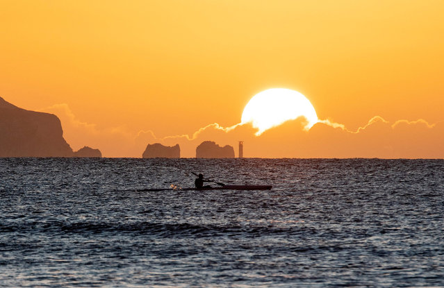 A kayaker is seen as the sun rises over The Needles, Isle of Wight, taken from Mudeford in Dorset on January 17, 2021. (Photo by James Marsh/Rex Features/Shutterstock)