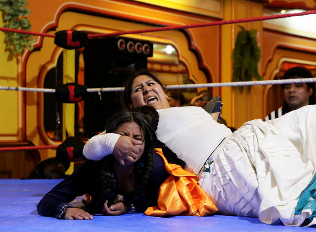 A Cholita (Andean woman) fighter makes a key to their opponent during a wrestling session at the Havana Hotel Cholet in El Alto, outskirts in La Paz, Bolivia on June 29, 2018. (Photo by David Mercado/Reuters)