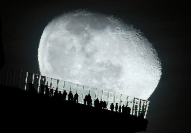 A waning moon rises behind people standing on the EdgeNYC outdoor observation deck at Hudson Yards in New York City on January 2, 2021 as seen from Hoboken, New Jersey. (Photo by Gary Hershorn/Getty Images)